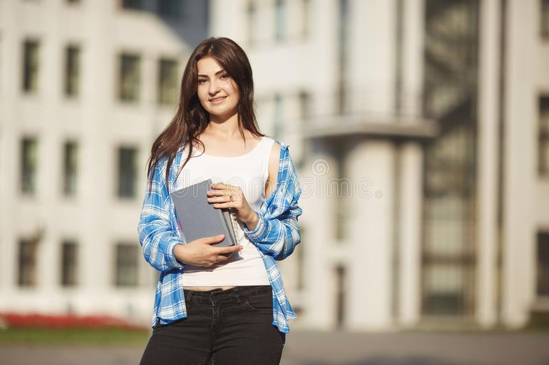 Student woman with books in hands standing on university buildin. G background. Campus life, holiday, education concept stock photo