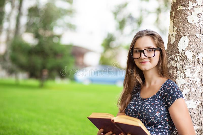 Student woman in glasses holding a book, looking at you smiling stock photos
