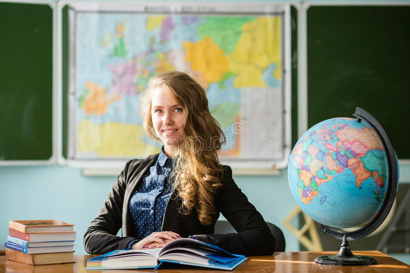 The student woman with globe in the classroom on blackboard background royalty free stock photo