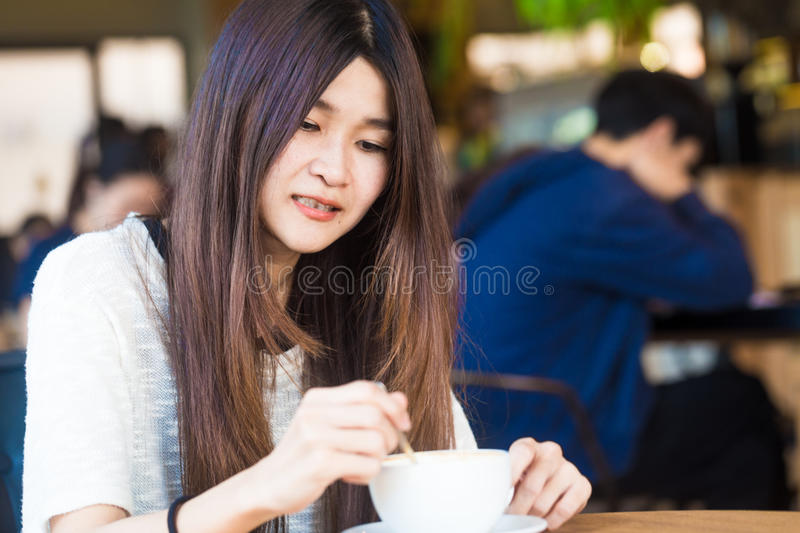 Student woman holding a cup of latte coffee in her hands at library background stock photo