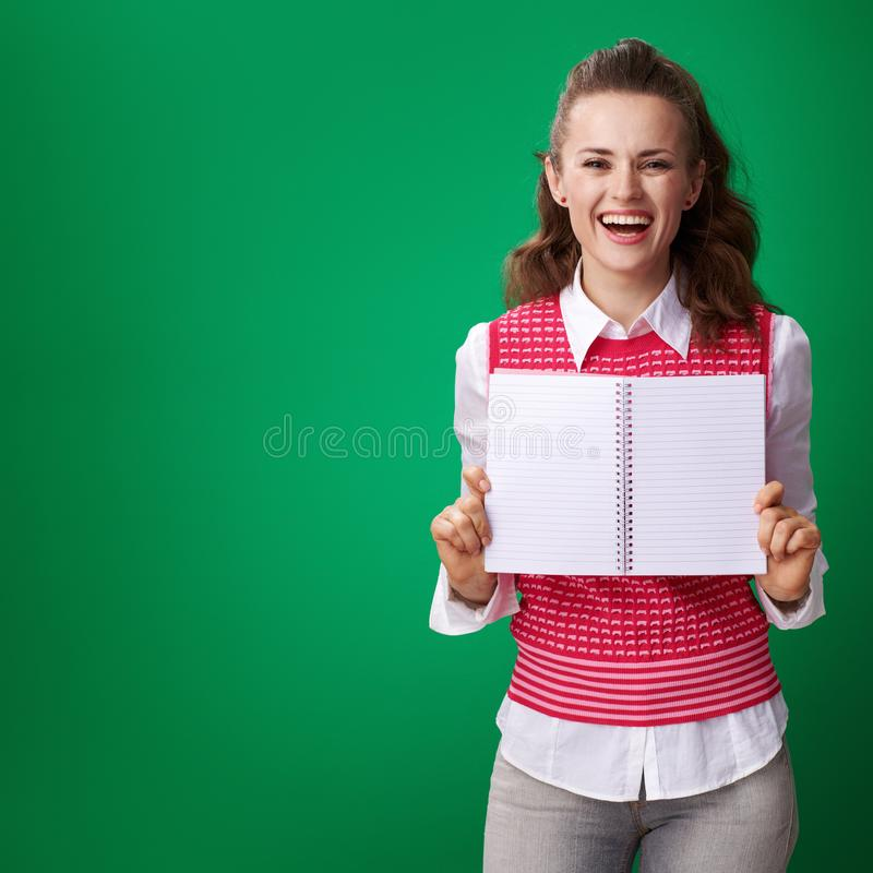 Student woman showing notebook blank page on green background. Happy young student woman in a red waistcoat showing notebook blank page on green background stock photography