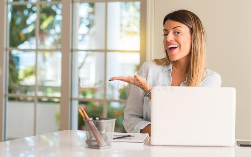 Young beautiful student woman with laptop at table, at home. Student woman at table with laptop at home holding something in empty hand stock image