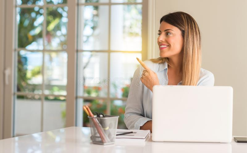 Young beautiful student woman with laptop at table, at home. Student woman at table with laptop at home pointing away side with finger royalty free stock image