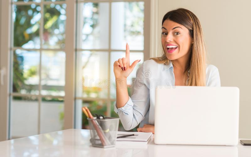 Young beautiful student woman with laptop at table, at home. Student woman at table with laptop at home pointing away side with finger stock images