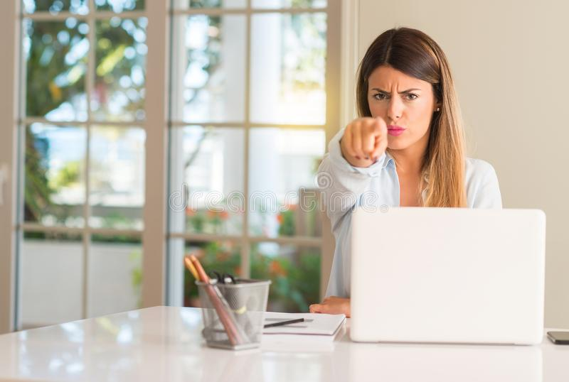Young beautiful student woman with laptop at table, at home. Student woman at table with laptop at home pointing to the front with finger stock image