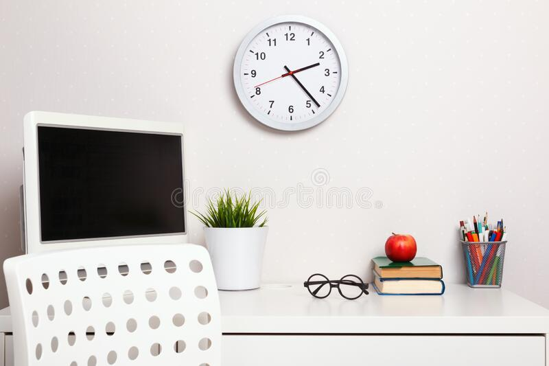 Student workplace. Closeup desk chair computer clock stack of books apple glasses stationery stock photography