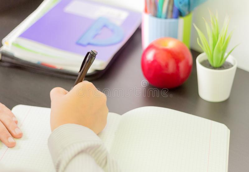 The student writes in a workbook, doing homework at the table royalty free stock photo
