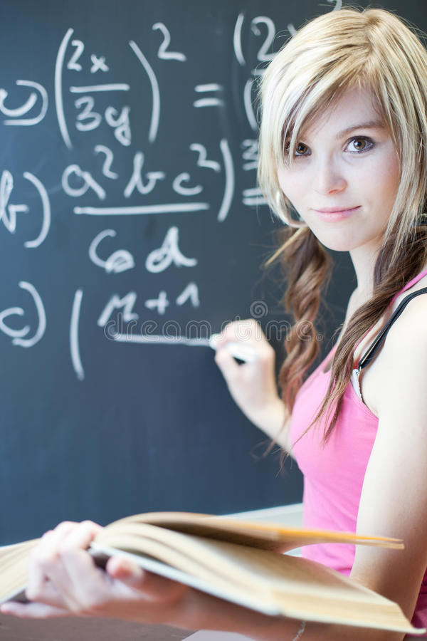 Student writing on the chalkboard. Pretty young college student writing on the chalkboard/blackboard during a math class (shallow DOF; color toned image royalty free stock images