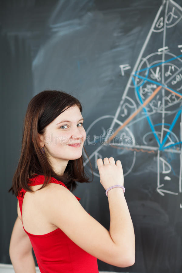 Student writing on the chalkboard. Pretty young college student writing on the chalkboard/blackboard during a math class (color toned image; shallow DOF stock photos