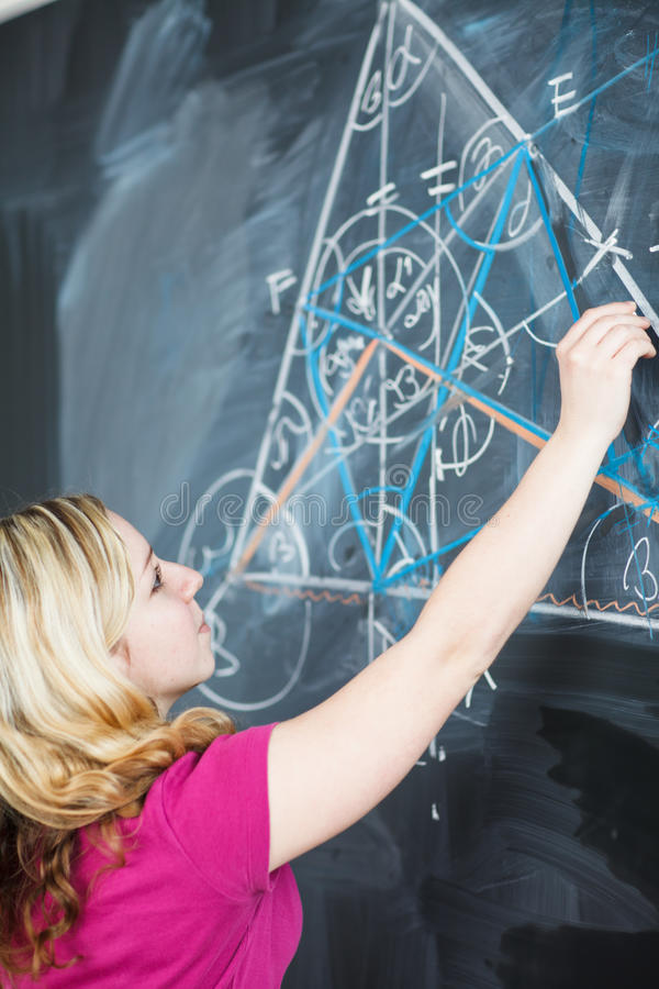 Student writing on the chalkboard. Pretty young college student writing on the chalkboard/blackboard during a math class (color toned image; shallow DOF stock images