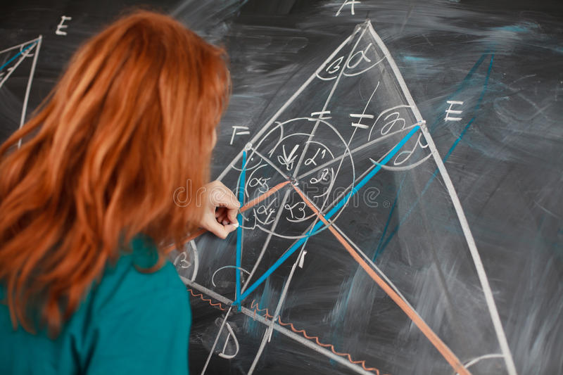 Student writing on the chalkboard royalty free stock photography