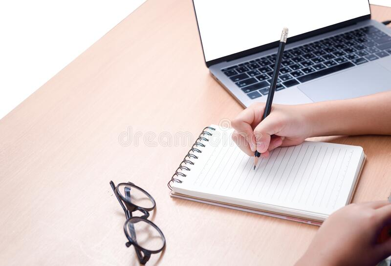 Student writing homework on blank notebook with laptop on desk royalty free stock photography