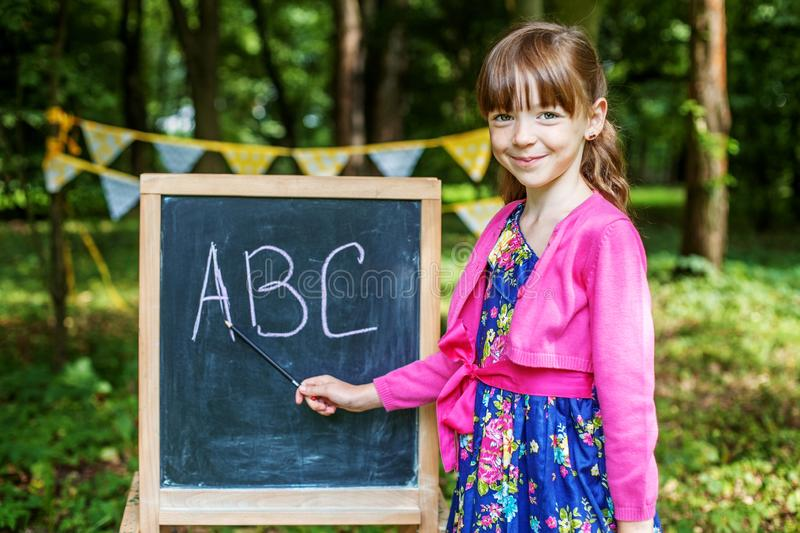 Student writing letters on a school board. The concept is back t stock image