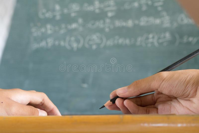 Student writing a note follow details on black board in classroom royalty free stock photography