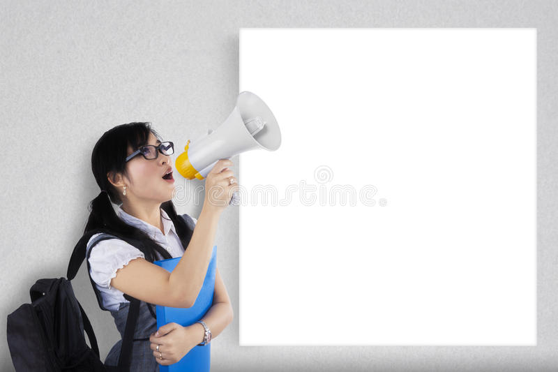 A student yelling near to copyspace. Portrait of a female student shouting via megaphone near to copyspace royalty free stock photo