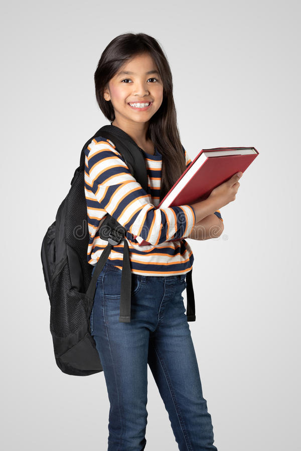 Student. Young asian girl standing and holding books, Isolated on grey background stock photography