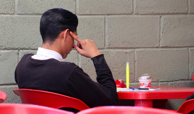Student. Young boy studies in a small cafeteria in his university, male student resting in common area in the outside of his school while he consume some dessert stock image