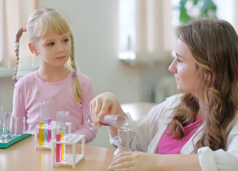 Student zeigt Experiment für das Mädchen stockbild