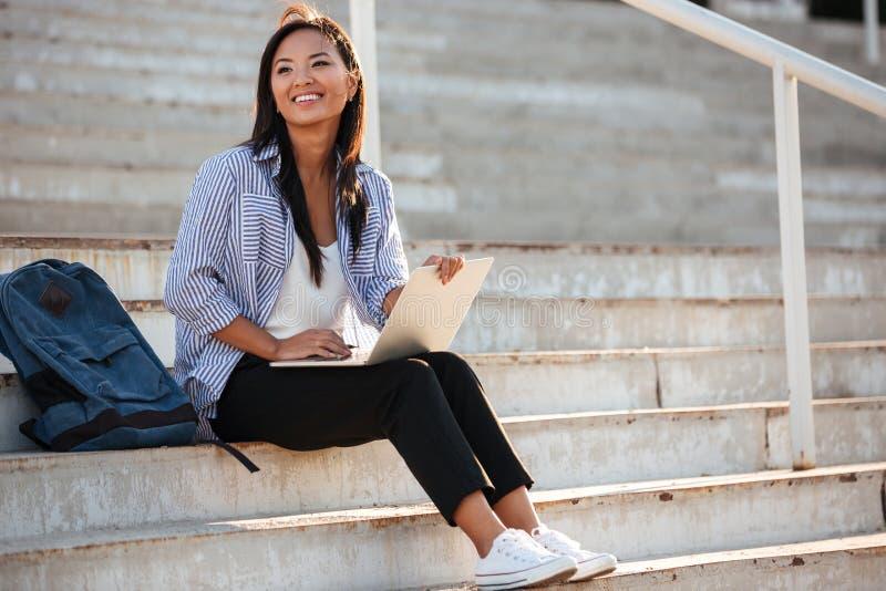 Studente asiatico abbastanza allegro dei giovani, tenente computer portatile, mentre sitti fotografia stock libera da diritti