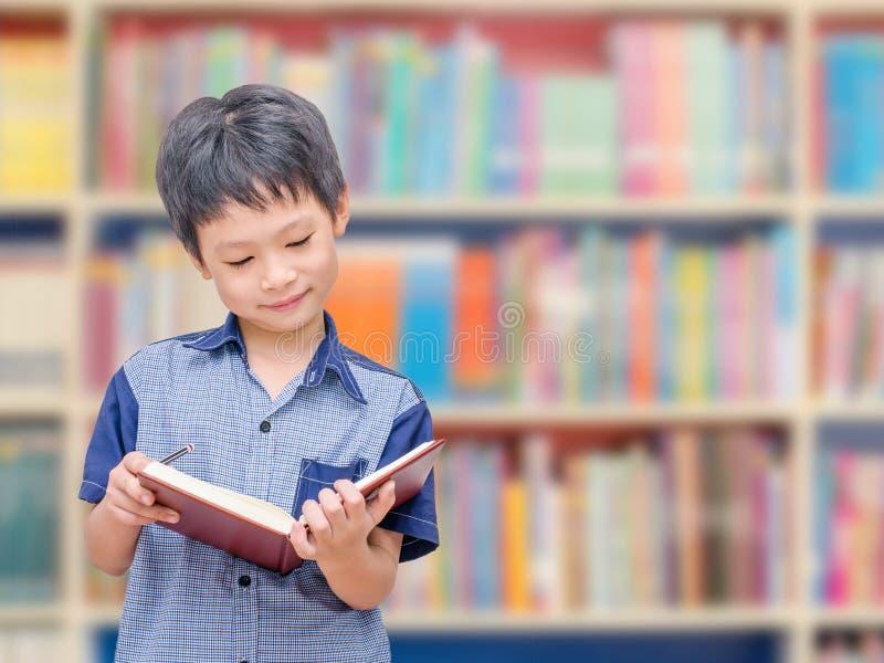 Studente asiatico del ragazzo nella biblioteca di scuola immagini stock libere da diritti