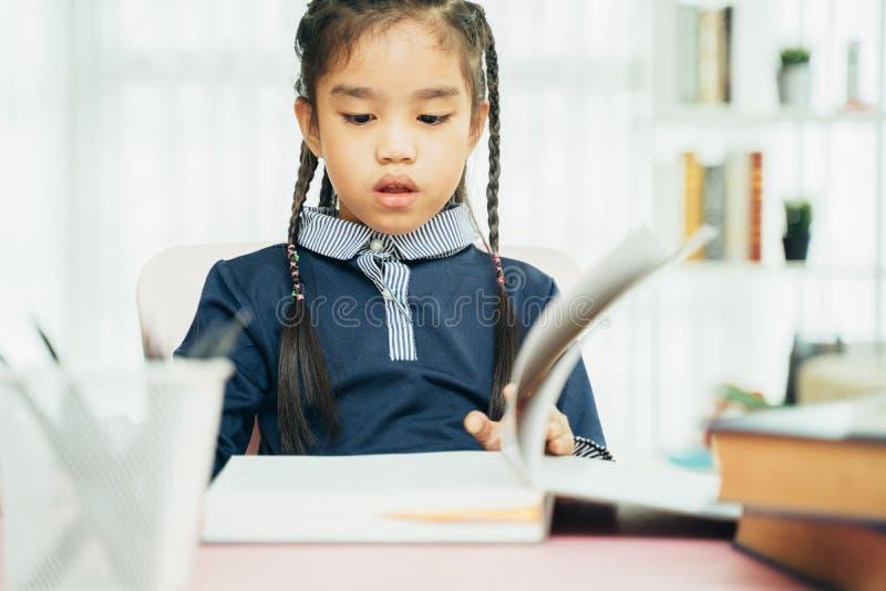 Studente asiatico della scuola primaria che studia compito in aula fotografia stock libera da diritti