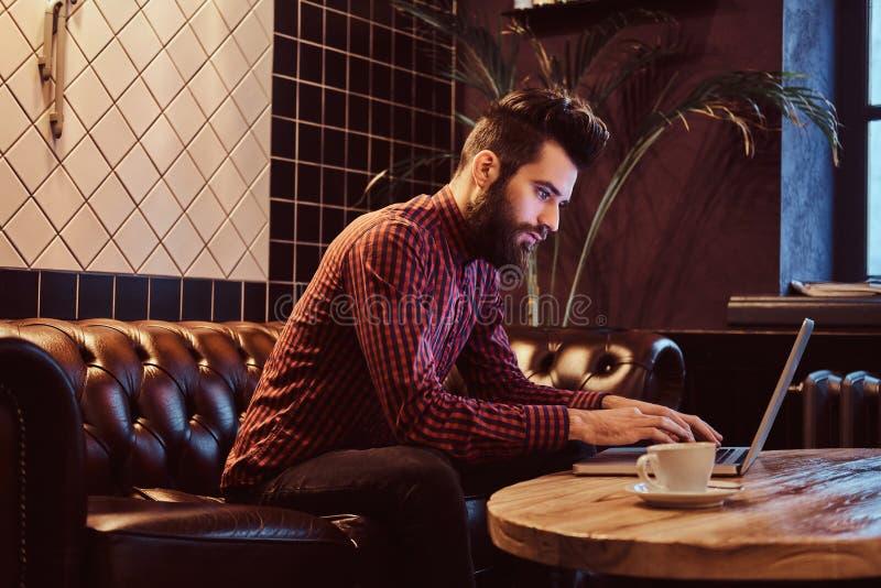 Studente barbuto alla moda durante la pausa che si siede sul sofà al caffè e che lavora con un computer portatile fotografia stock libera da diritti