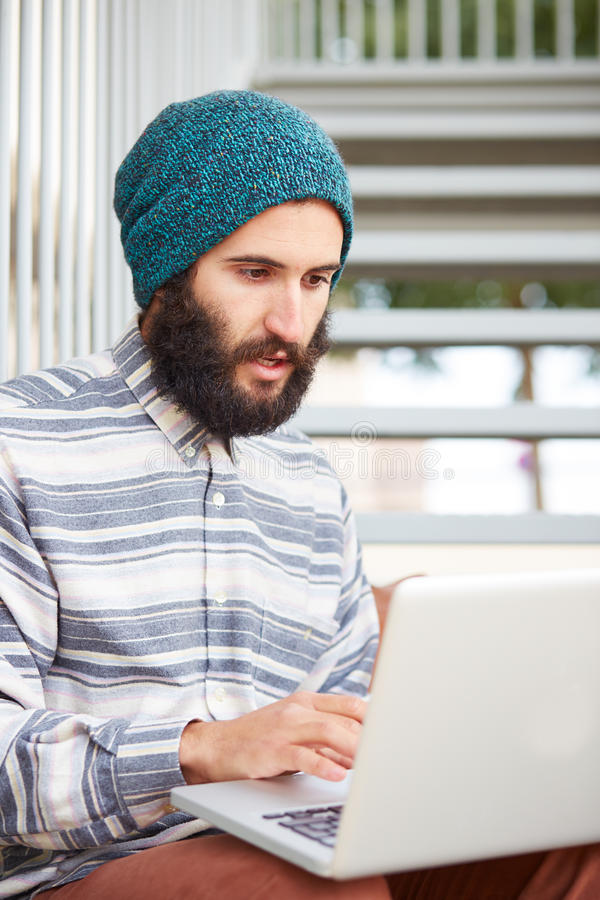 Studente barbuto giovane dei pantaloni a vita bassa che per mezzo del computer all'aperto immagine stock