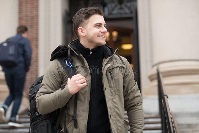 Studente bello che cammina nella città universitaria dell'istituto universitario con uno zaino alla classe fotografia stock libera da diritti