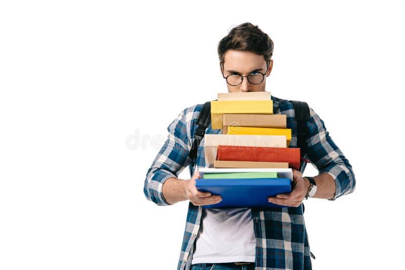 studente bello che guarda fuori dalla pila di libri fotografie stock