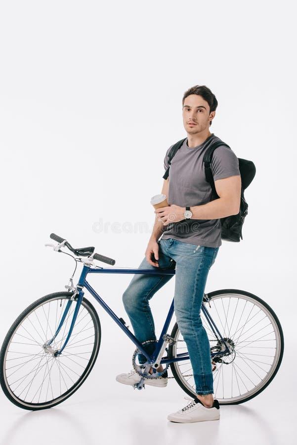 studente bello che si siede sulla bicicletta e che tiene caffè per andare immagine stock