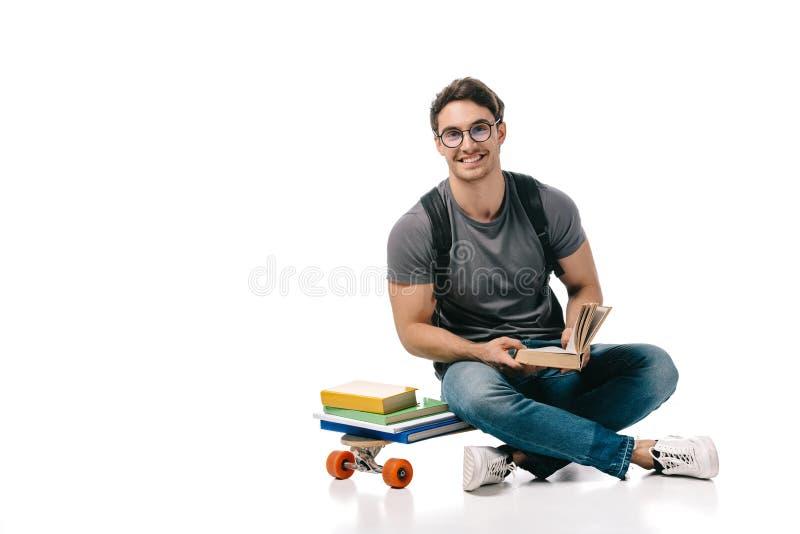 studente bello sorridente che si siede sul pattino e sulla tenuta del libro immagini stock
