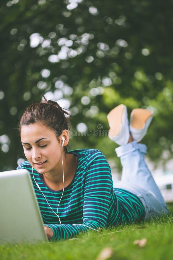 Studente casuale contento che si trova sull'erba facendo uso del computer portatile fotografie stock libere da diritti