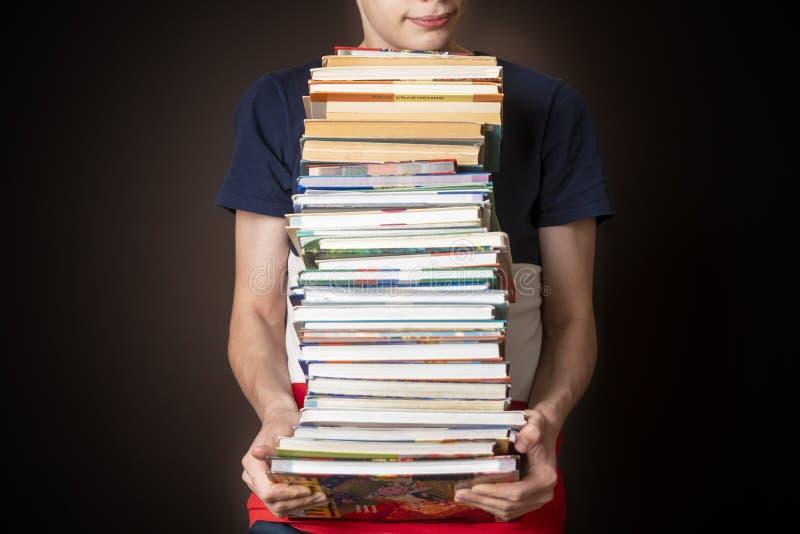 Studente casuale portare pila enorme di libri su fondo scuro f fotografia stock libera da diritti