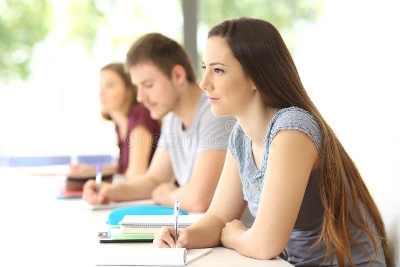 Studente che ascolta una lezione in un'aula fotografie stock