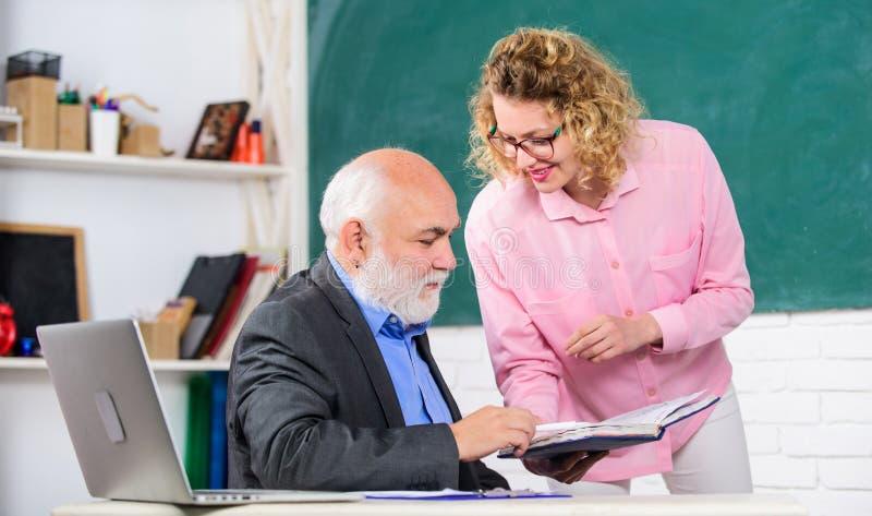 Studente che chiede all'insegnante riguardo al compito Educatore ed allievo che esaminano libro Spiegazione delle informazioni di fotografie stock
