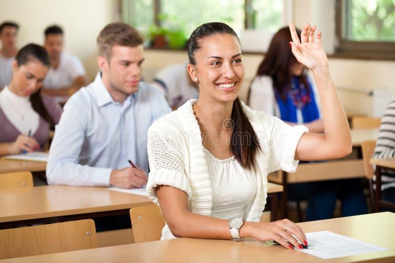Studente che dà risposta nella classe con la sua mano sollevata fotografia stock libera da diritti