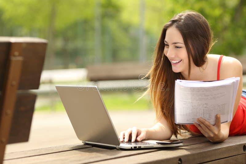 Studente che impara con un computer portatile in un campus universitario fotografia stock