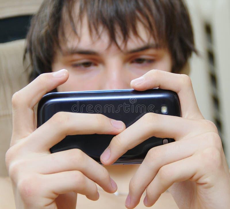Studente che invia messaggio di testo fotografie stock