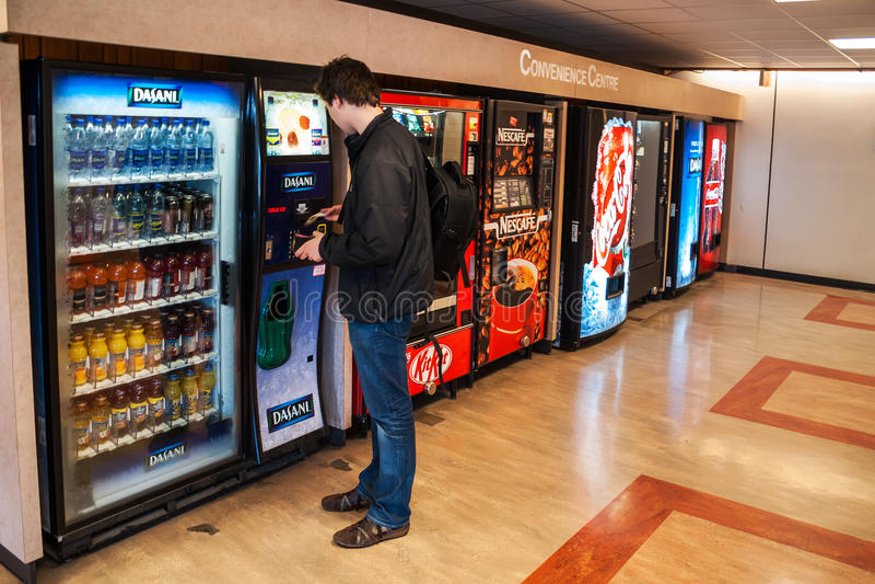 Studente che paga le bevande dal distributore automatico immagini stock libere da diritti