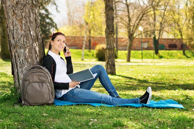 Studente che parla sul telefono in un parco immagine stock