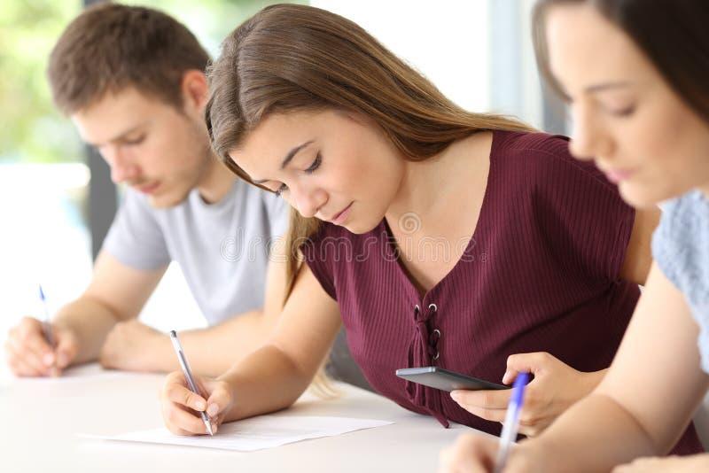 Studente che per mezzo di uno Smart Phone durante l'esame fotografia stock