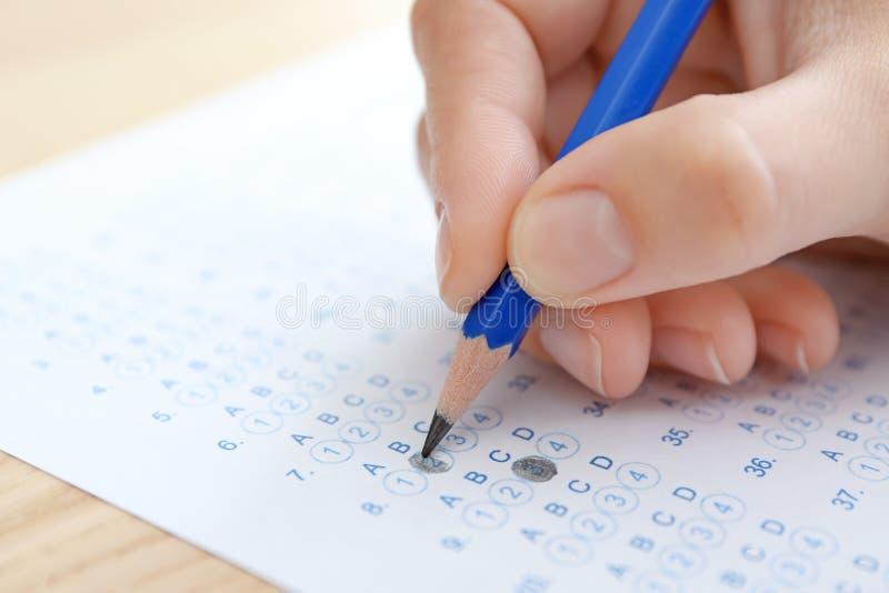 Studente che sceglie le risposte nella forma della prova per passare esame fotografia stock libera da diritti