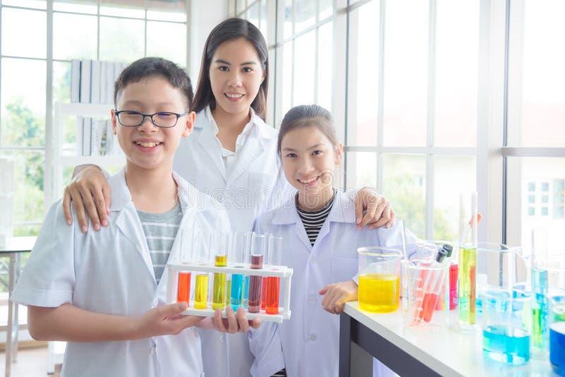 Studente che sorride con il loro insegnante nell'aula di chimica immagini stock