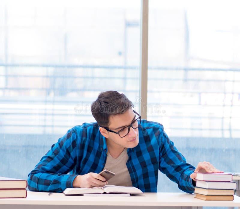 Studente che studia nella biblioteca vuota con il libro che prepara per ex immagini stock libere da diritti