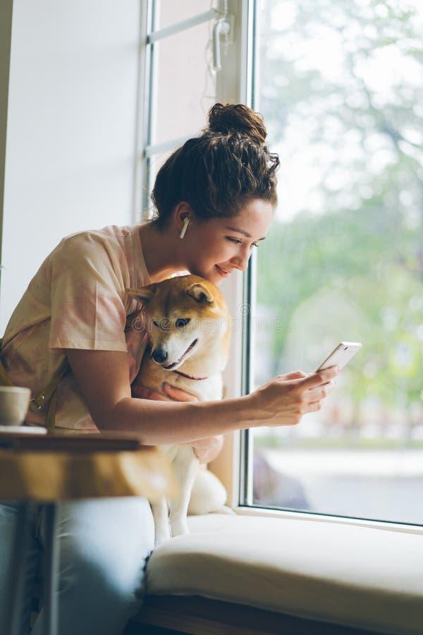 Studente che utilizza smartphone che gode della musica nelle cuffie che segnano cane in caffè immagine stock libera da diritti