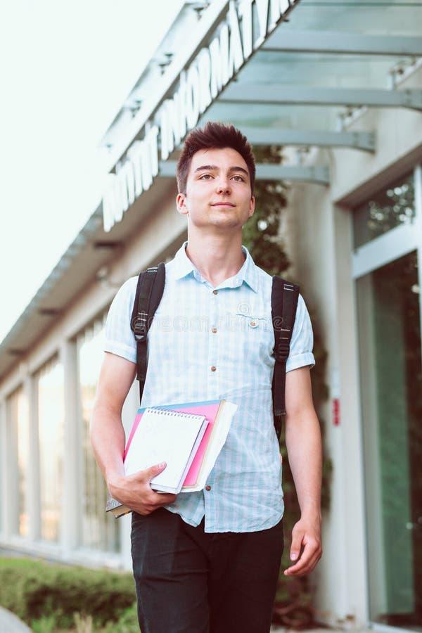 Studente con i libri che cammina alla parte anteriore dell'università immagini stock libere da diritti