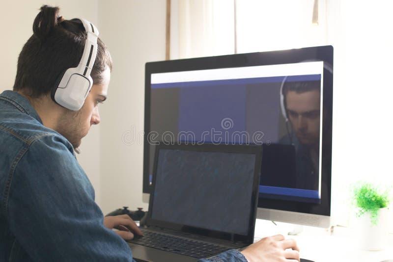 Studente con los auriculares y el ordenador imagenes de archivo