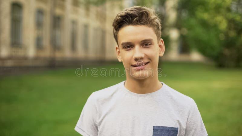 Studente contro l'università che sorride alla macchina fotografica, programma del cambio sull'estero per gli anni dell'adolescen fotografia stock