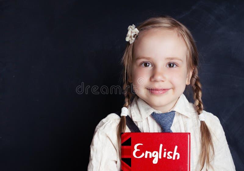 Studente della bambina con il libro inglese vicino alla lavagna immagine stock
