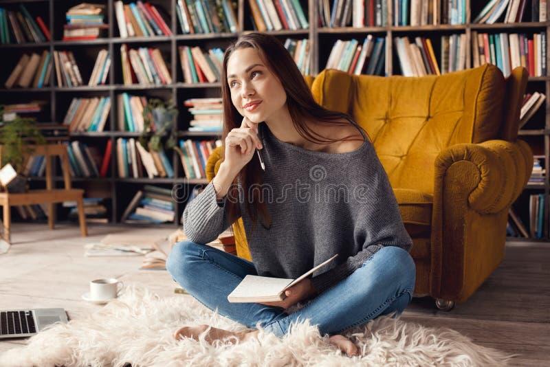 Studente della giovane donna in biblioteca a casa che si siede cercare sognante fotografia stock libera da diritti